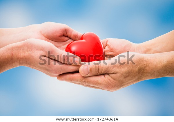 Red heart in human hands on blue sky background