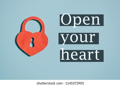 A red heart with a keyhole on a blue paper