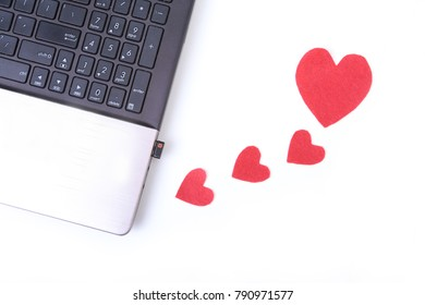 Red heart with laptop on wooden table
