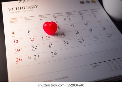 Red heart laying on calendar Valentine's day