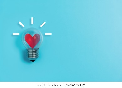 Red heart in light bulb on blue background with copy space. Valentine's day, Creative idea, Inspiration Concept.