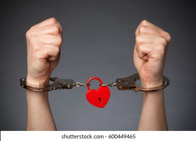 Red Heart Lock and Handcufs on a pair of hands: Being trapped by Love