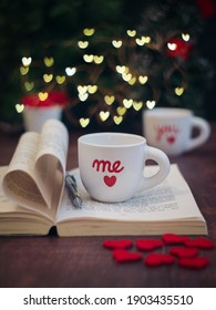 A red heart lovers coffee mug with pen put on an open book page fold in heart shape, me and you letters wrote on, cozy atmosphere with light of mini heart bokeh in background. Valentine's day concept
