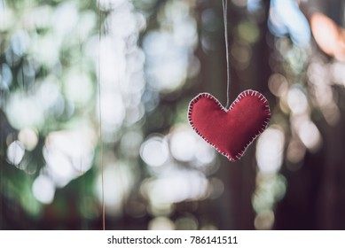 Red heart made with velvet cloth hanging on the Natural blur  background .Valentine 's Day Concept.