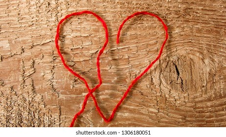 Red heart made of red yarn on a textured wooden background. Can be used for the concept of romance, love, engagement, Valentine's Day, marriage, wedding, etc. Close-up.