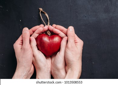 Red heart in man and woman hands on old dark wooden table