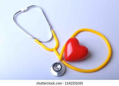 Red heart and a medical stethoscope on desk