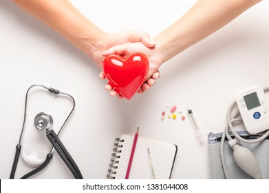 Red heart model on a couple  hands holding, Top view of plastic red heart, stethoscopes, Automatic portable blood pressure and drugs on white background, medical and healthy or antenatal care concept.