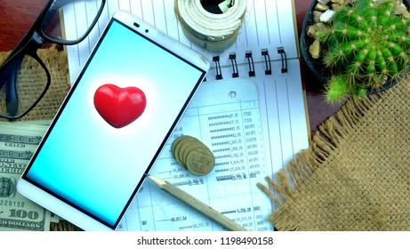Red heart ,money coins and roll of bank on statement bank report.Saving money for health and future.Insurance themes, retirement planning ,travel and investment ideas, passive income.education plan