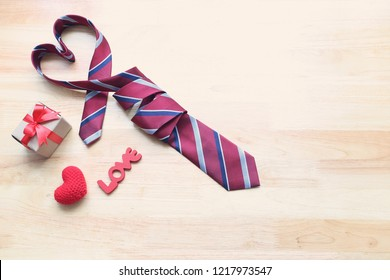 Red heart necktie and gift box with red ribbon and handmade crochet heart on wood background for happy fathers day