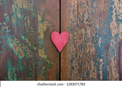 A red heart on a colorful wooden background