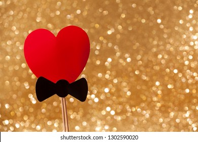 Red heart on a golden background with a shining golden glitter effect. Holiday card. Carnival. Mardi gras. Masquerade. Place for text. Valentine's Day. The concept of the holiday Purim. photo booth.