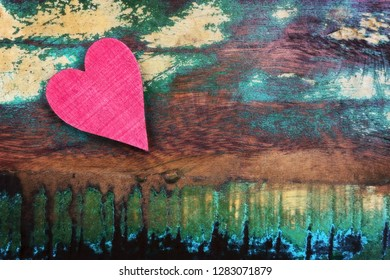 A red heart on an old wooden background