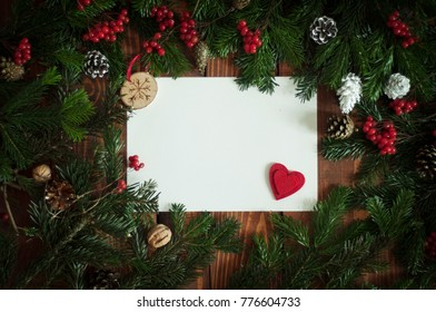 Red heart on the piece of paper framed with pine tree branches and red berries. Merry christmas decorative frame. Banner, poster or greeting car template on Merry Xmas.  Christmas tree