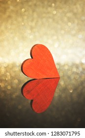 Red heart on reflective surface and an illuminated background