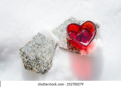 A red heart on a stone slab in the snow