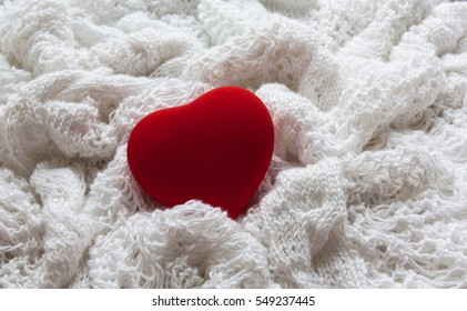 Red heart on a white background. The background is made of knitted fabric.