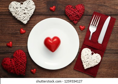 Red heart on white plate with kitchen cutlery on wooden table