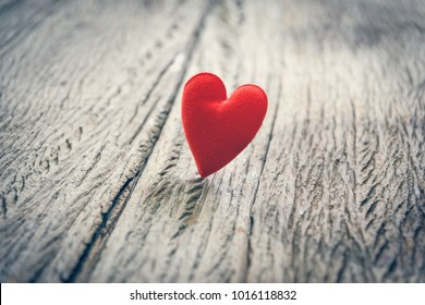 Red heart on wooden floor with copy space for text, used in love concept on Valentine's Day.