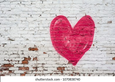 A red heart painted on a distressed white brick wall.