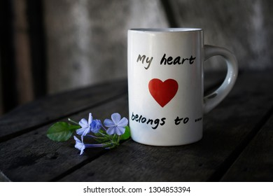 Red heart painted on a white coffee mug on an old wooden table. Valentines day concept.
