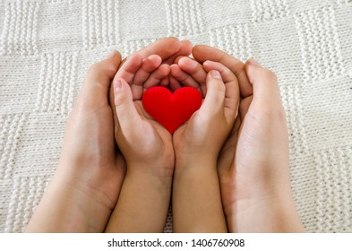 Red heart in the palm. Children's hand in an adult hand on a beautiful light background. Hand on hand.