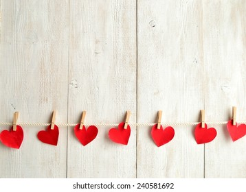 Red heart paper cut with clothes pin on white wooden background.Image of Valentines day