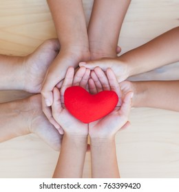 Red heart in parent and children holding hands together on wooden background. Family and friend stack hands with red heart showing unity, teamwork and love