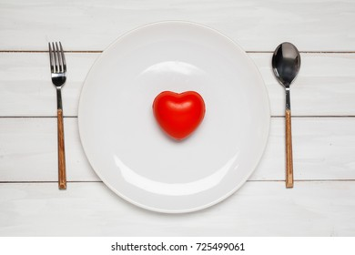 Red heart and plate top view on white plank wooden background