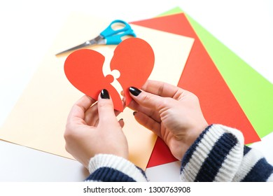 Red heart puzzle. Woman hands holds two part of paper heart. Happy Valentine's day. Be in love. Female hand matching red puzzle heart halves. Concept of love