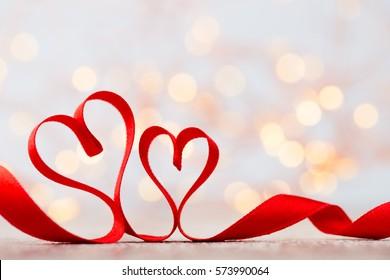 Red heart. Red ribbon heart shape. Bokeh background.