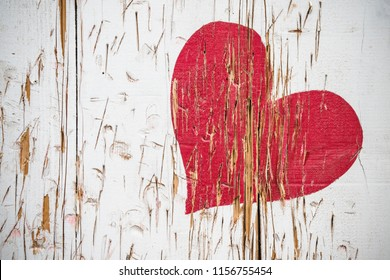 Red heart scratched in wood in red color on a wooden surface