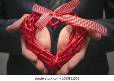Red heart shape in businessman hands. Gift of love. Love present. The proposal concept background. An offer of marriage.