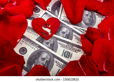 red heart shape with a dollar sign inside lies in a dollar currency background with red rose petals. Love money