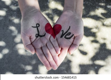 Red heart shape drawn on woman's palm, forming the word love