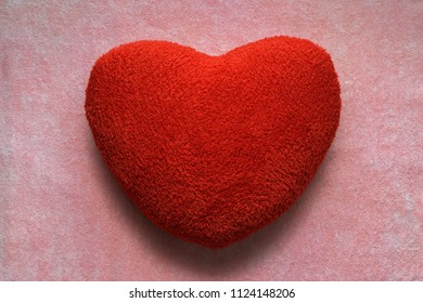 Red heart shape fluffy pillow  on pink carpet background