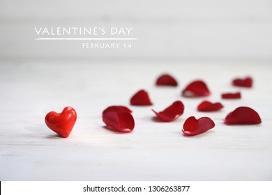 red heart shape from glass and rose petals on a light grey wooden background, text Valentine's Day February 14, love concept with copy space, selected focus, narrow depth of field