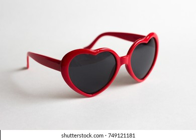 Red heart shape glasses isolated on white background. Lolita by Nabokov concept.