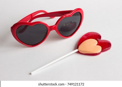 Red heart shape glasses with heart lollipop isolated on white background. Lolita by Nabokov concept.
