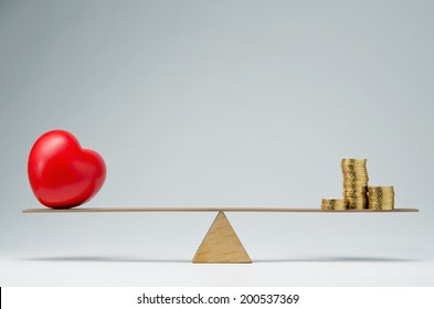Red heart shape and money coins stack balancing on a seesaw