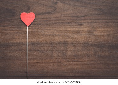 red heart shape on stick over wooden background