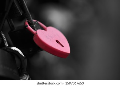The red heart shape padlock hanging in the middle of many blurred padlocks that around and all are at the fence of the bridge in Paris, France. Concept Padlocks Love forever. Valentine.