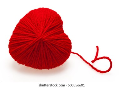 Red heart shape symbol made from wool on a white background. Valentine's Day, Wedding composition with the heart.