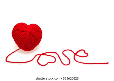 Red heart shape symbol made from wool on a white background. Valentine's Day, Wedding composition with the heart