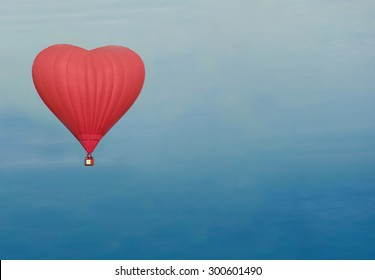 red  heart shaped balloon in the sky