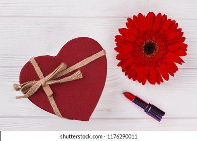 Red heart shaped box, lipstic and daisy flower. White wooden background. Top view.