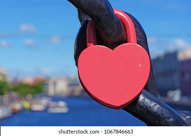 A red heart shaped lock connected to chain, canal with boats in the background.