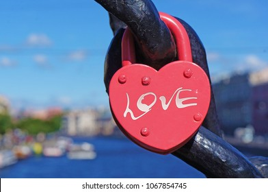 A red heart shaped lock with the inscription love, canal and boats on the background.