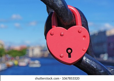 Red heart shaped lock with keyhole, canal with boats on the background.