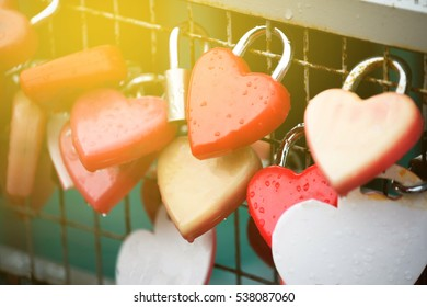 Red heart shaped lock padlock on the fence on the background, Sun light flare , Soft focus